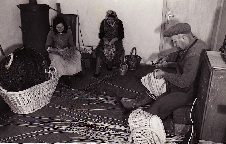 A black-and-white photo of two women and a man weaving baskets