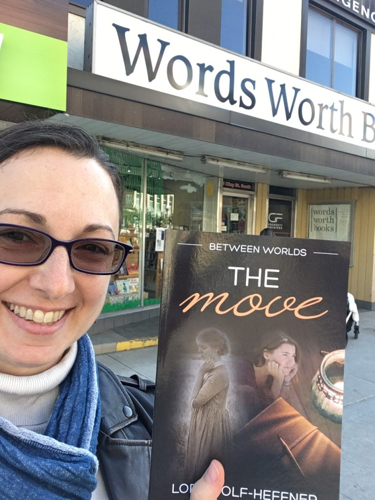 """Canadian author Lori Wolf-Heffner holds a copy of """"Between Worlds 1: The Move,"""" the first in her young adult series about dance, in front of Words Worth Books in Waterloo"""
