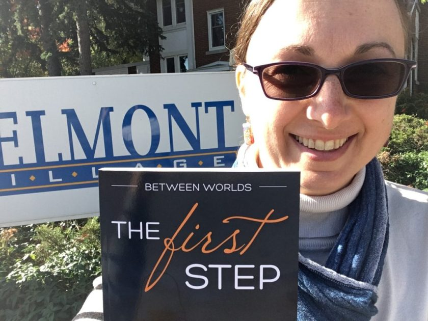 """Canadian author Lori Wolf-Heffner stands outside the Belmont Village sign in Kitchener, holding a copy of her book, """"Between Worlds 3: The First Step."""""""