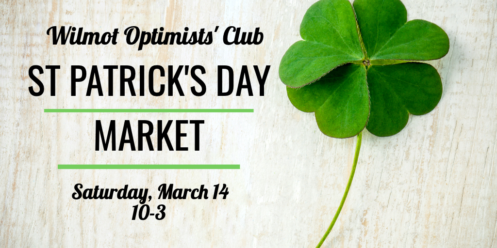 A 4-leaf clover on light-grey wood and information about the Wilmot Optimists' Club St. Patrick's Day Sale