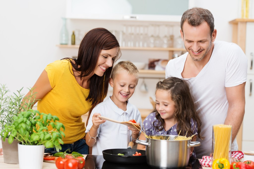 A mother, father, and two young children standing by the stove, cooking pasta and pasta sauce