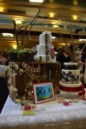Tall twigs with fabric roses and pearls frame my stall...