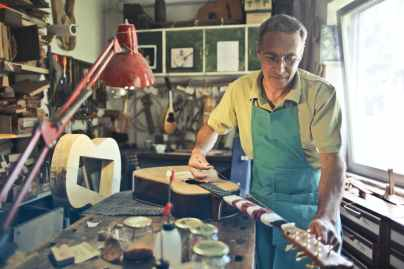 photo of man making an acoustic guitar