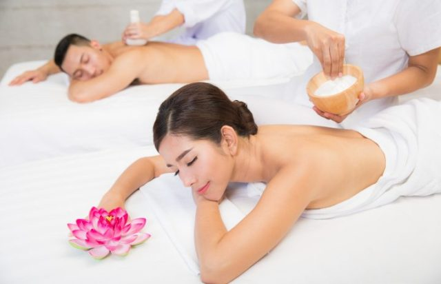 Young couple lying on the massage table and smiling