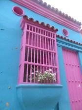 Preciosas y coloridas fachadas con ventanas enrejadas.