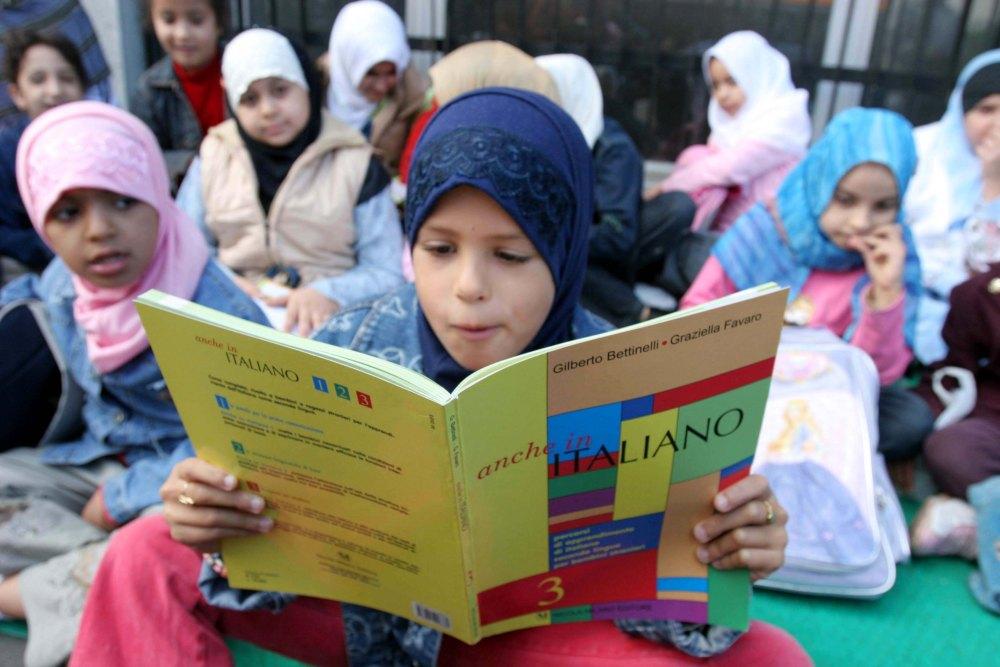 Una bambina legge un libro di testo italiano durante la  lezione tenuta davanti ad una scuola di Milano