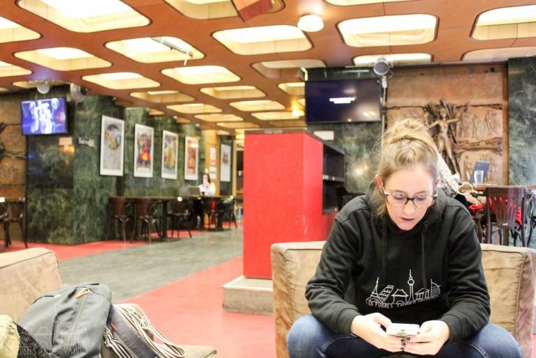 Marina sentada en un sofá del café escribiendo en el móvil.