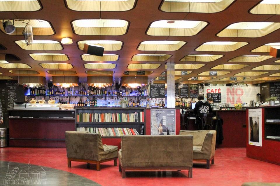 Café nona con la barra al fondo, sillones y sofás en el medio y librería detrças de ellos. Moqueta de color rojo y techo con apliques de forma cuadrangular.