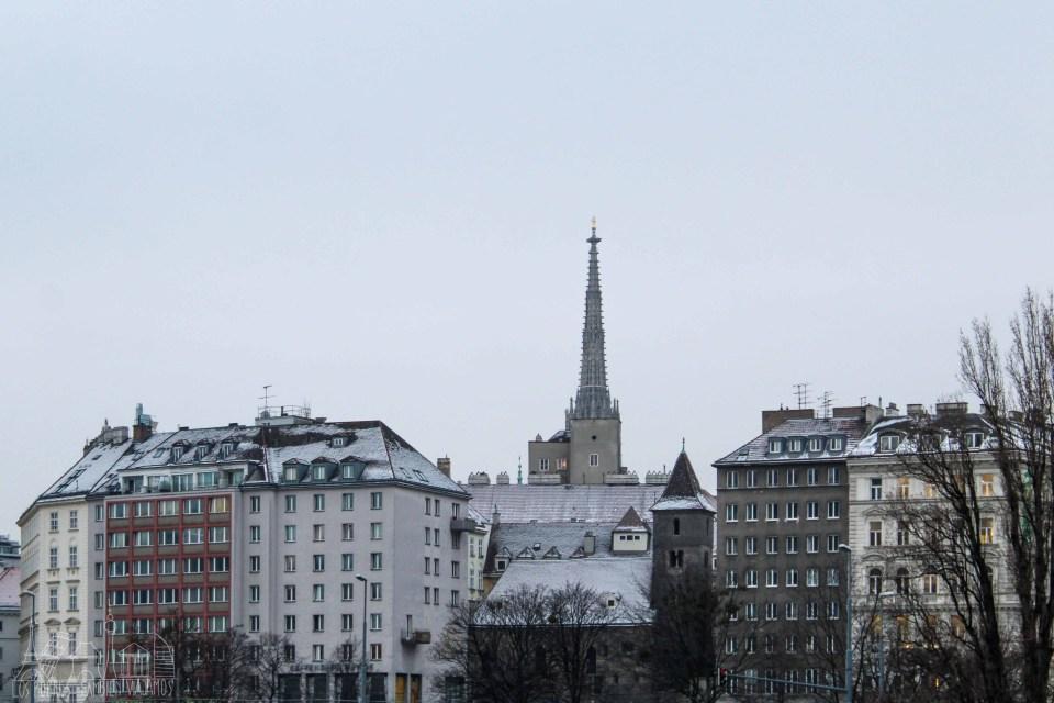 Panorámica de Viena con la torre de la catedral despuntando en el medio. Edificos de pocas plantas con tejados a cuatro aguas y nevados.  Pequeña iglesia medieval en medio de dos bloques de edificios.
