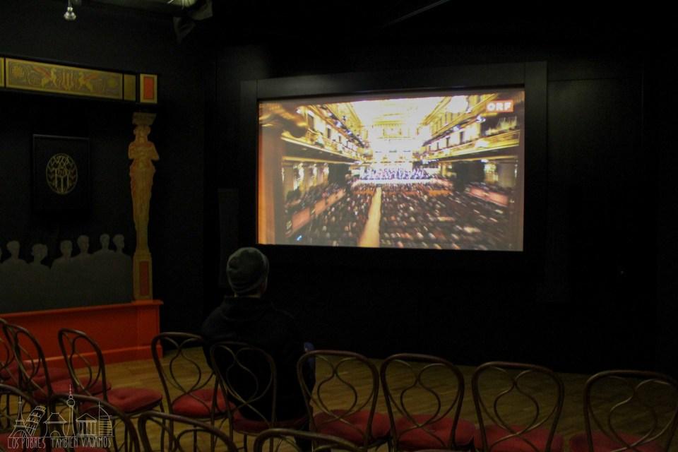 Juanjo sentado en una silla dispuesta a modo de teatro viendo, en una pantalla de cine, una concierto de la Filarmónica de Viena.