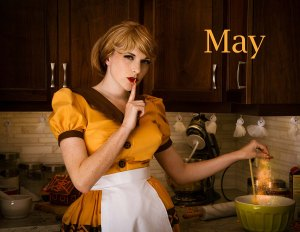 Lossien standing in a kitchen, wearing a yellow 50's style dress and light brown wig. She is holding one finger to her red lips in a 'silence' gesture, and putting magical particles into a bowl on the counter. The word 'May' is on the top right.