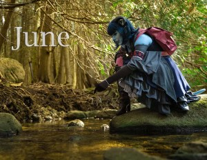 Lossien dressed as Jester, with blue skion and a blue wig, wearing a grey dress and pink backpack,. She is on the right of the image, bent over and poking a rock on the left of the image with a stick. The word 'June' appears on the upper left of the image.