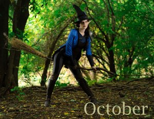 Lossien as Witch Vex. Wearing a black witch hat, a blue tail coat and black and grey striped pants, Lossien is holding a broom between her legs and standing in a lush green forest. The word 'October' appears in the bottom right.