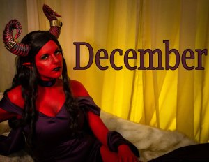 Lossien as the Ruby of the Sea, on the left of the photo, with red skin and horns, and dark brown hair, in a dark purple dress. The word 'December' appears across the center to right of the image.