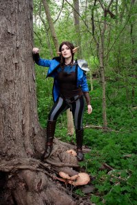 Lossien standing on the roots of a tree, one arm leaning on the trunk. She is wearing a long brown wig and elf ears, with a blue tail coat, a brown corset, and black and grey striped pants.