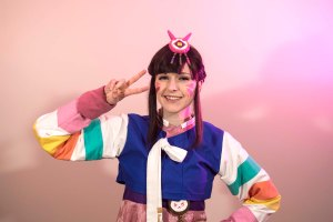 Lossien in front of a pink background. Wearing a multi-coloured hanbok of mainly pink, with blue, white and coloured details. She has a brown wig on, and a small D.Va symbol in pink on her head. She is giving the peace sign right beside her face.