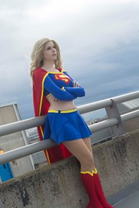 Lossien standing at the edge of a building as Supergirl, with blonde hair, a blue long sleeved cropped shirt and skirt, with yellow details and a red cape and boots.