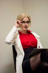 Lossien holding the edge of her glasses while wearing a blonde wig, white lab coat, red shirt and black high waited pencil skirt.
