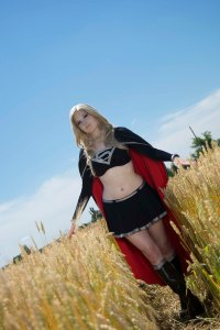 Standing in a field of wheat, Lossien is wearing a blonde wig and a black, long sleeve cropped shirt and matching skirt, and a red lined cape.