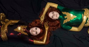 Lossien layong on the left in a dark red bodysuit with gold details, and laying on the right in a green bodysuit with gold details.