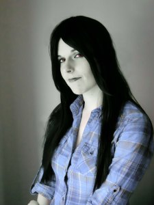 Lossien as Merceline. Grey skin, a long black wig, and red eyes, with a faded blue plaid shirt.