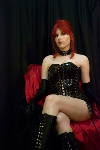 Lossien in a black PVC corset, boots and, collar and gloves, with a red wig, sitting on a red chair.