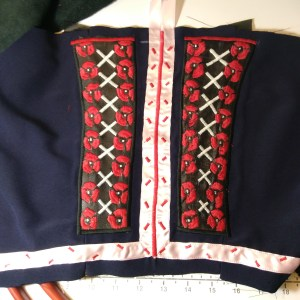 A blue bodice with pink stripes down the middle and along the bottom, and black rectangles to either side with red flowers on it.