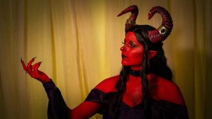 Lossien as the Ruby of the Sea. A portrait of her with red skin and horns, and long brown hair. She is wearing a dark purple dress and raising one hand to the left in the photo.