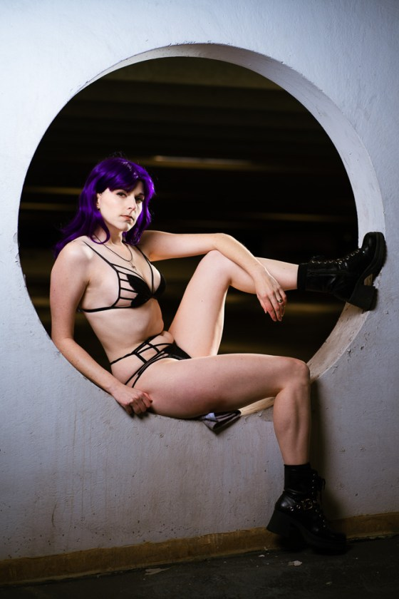 Lossien lounges in a circle, wearing a purple wig, black butterfly shaped lingerie, and short combat boots.