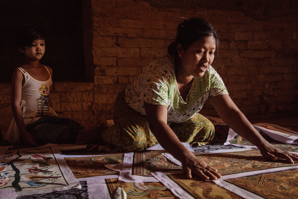 Photo of a Burmese woman inside of a temple in Bagan, Myanmar showing her artwork.
