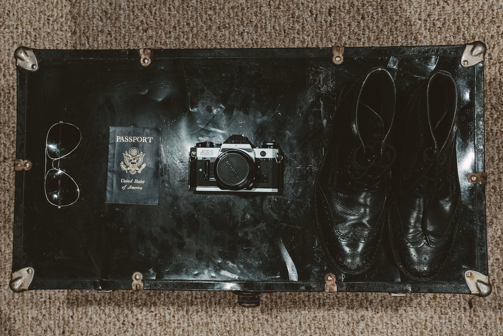A vintage trunk with passport, a canon AE-1 Program, and vintage shoes.