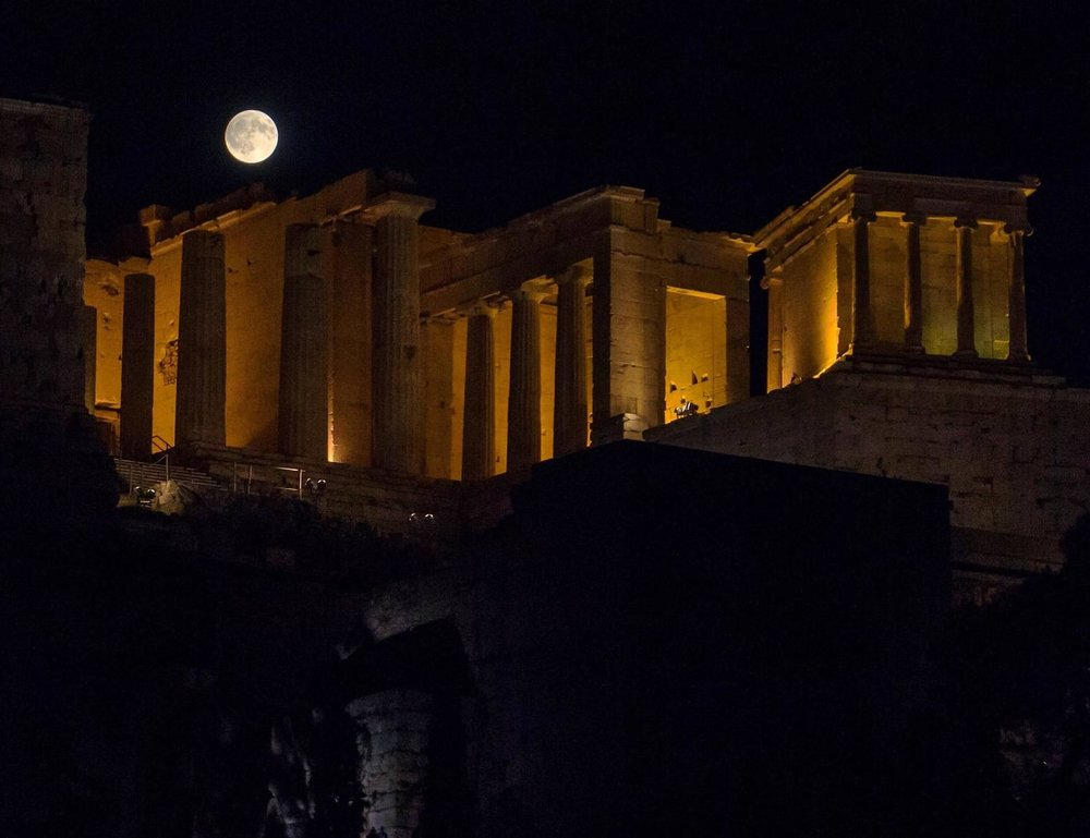 Photo of the full moon rising over the Acropolis at night.