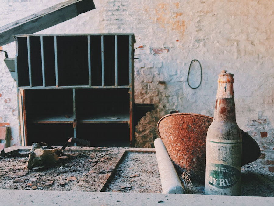 Old dusty rum bottle in an abandoned coffee factory in Jacmel Haiti.