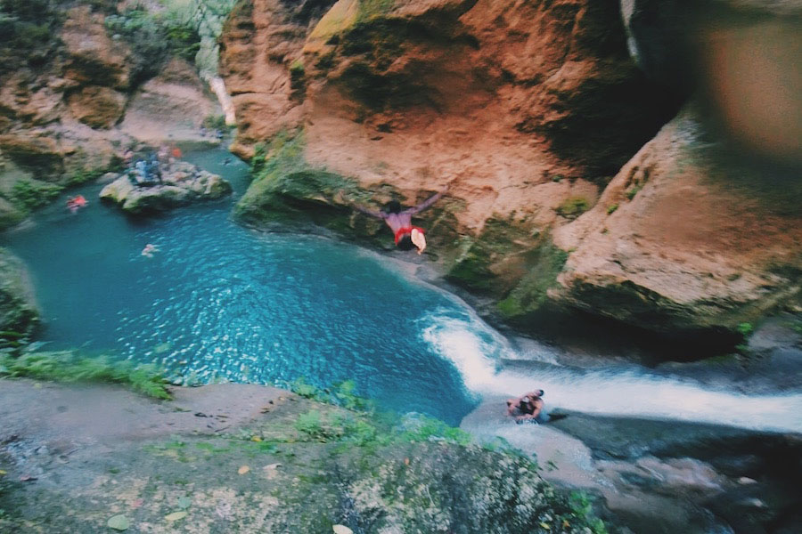 A Haitian boy jumps off a waterfall in Bassin Bleu near Jacmel Haiti.