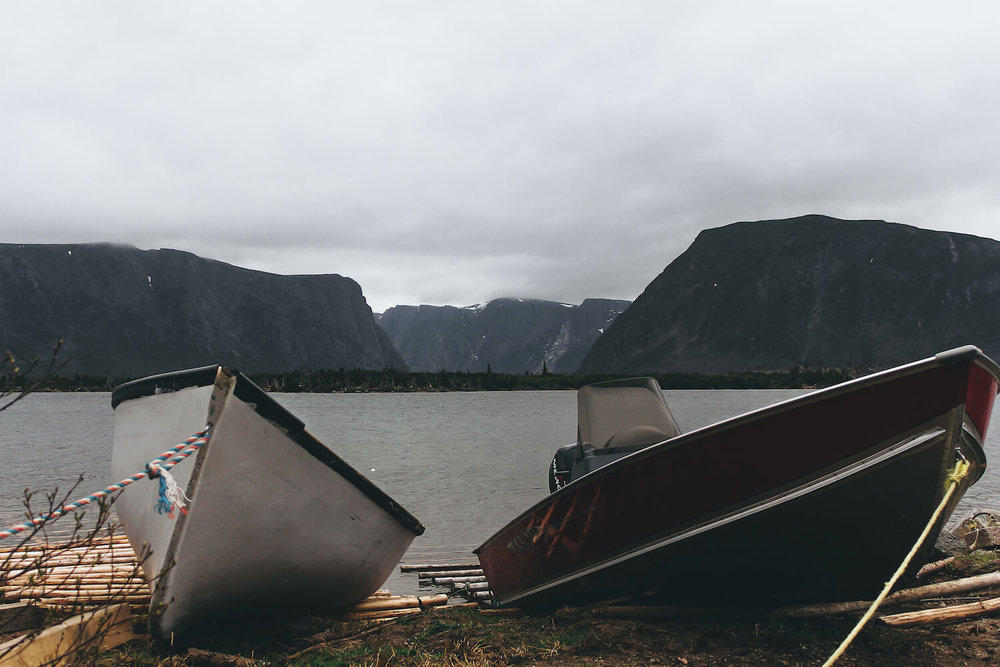 Photo of Gros Morne Nation Park in northeastern Canada. Two small boats pulled up on shore out of the black lake the stretches to the Fjord of Gros Morne.