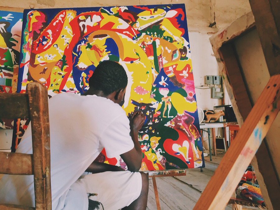 A young Haitian art student works on a painting of voodoo style expressionism. Paintings in an old abandoned coffee factory in Jacmel Haiti featuring traditional Voodoo and modern Haitian artwork.