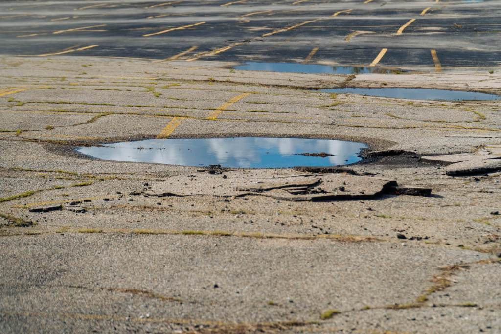 Photo of a puddle of water reflecting the blue cloudy sky on cracked asphalt.