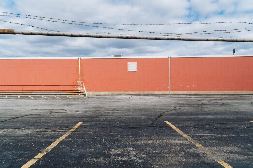 Photo of an empty lot and abandoned building with barbed wire.