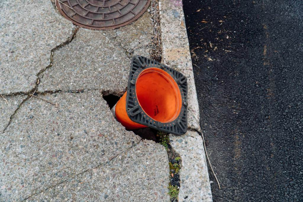 A photo of a traffic cone upside down in a hole in the sidewalk.