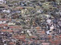 Detail of wall of old church highlighting flint and Roman tile used in construction