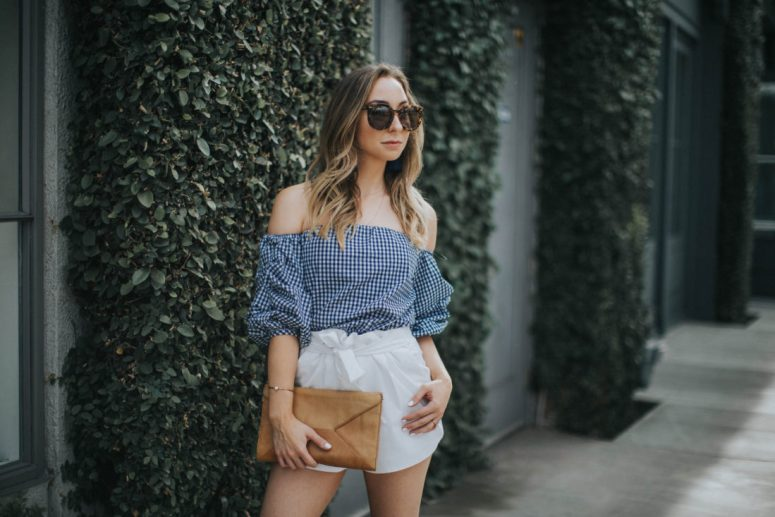 Spring Outfit : Tortiose Karen Walker sunglasses, Blue gingham off the shoulder top, white bow shorts, tan leather clutch