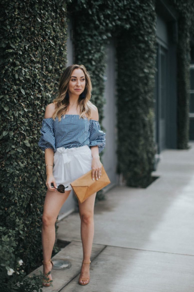 Blue gingham top, white bow shorts, nude heels, tan clutch, tassel earrings