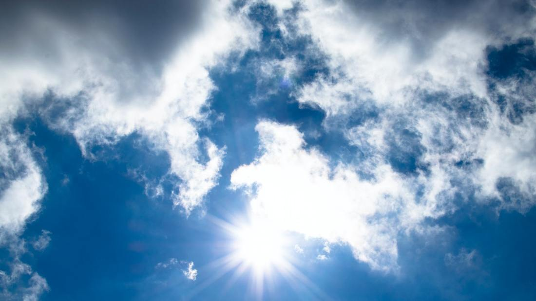 blue sky with clouds and bright sun