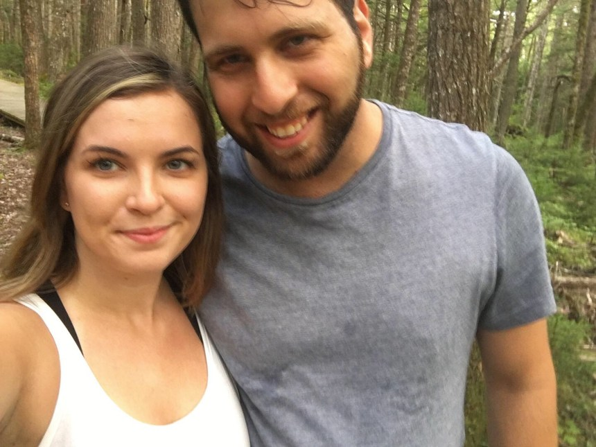 Cute couple on a special hike walking at a national park with lots of trees and green moss