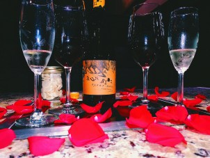 romantic table set for a special anniversary date with red rose pedals, wine glasses and a bottle of wine
