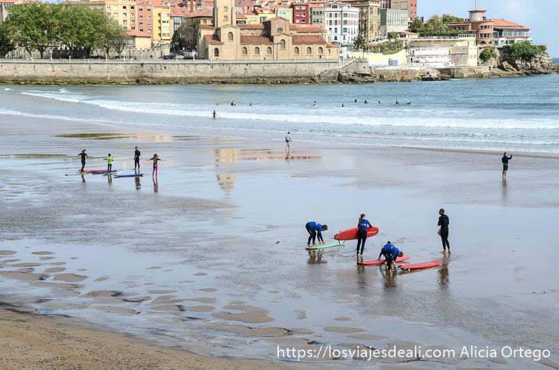 surfistas vestidos de azul en la playa de gijón