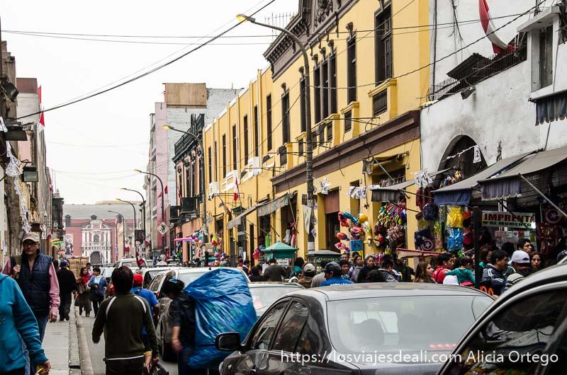 calle del mercado central llena de coches, gente y mercancías