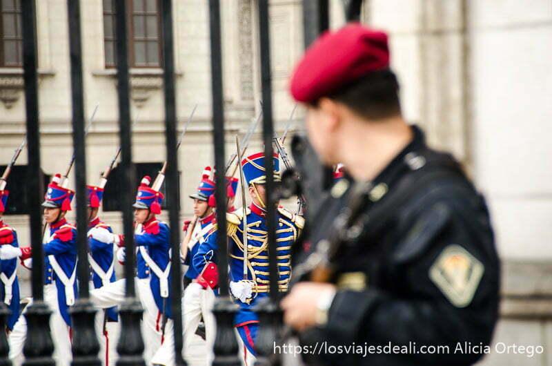 soldado observando entre los barrotes de la valla la marcha militar