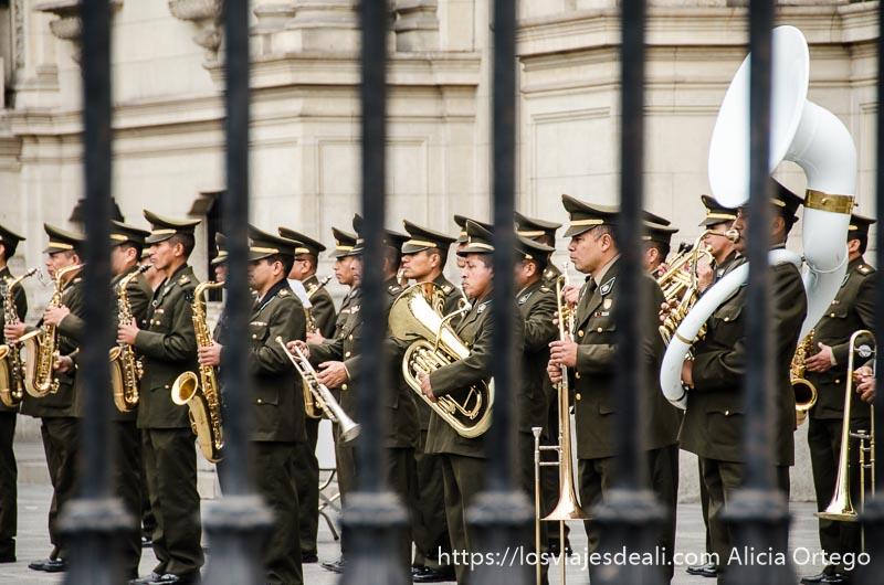 banda de música militar con trompetas y un trombón blanco
