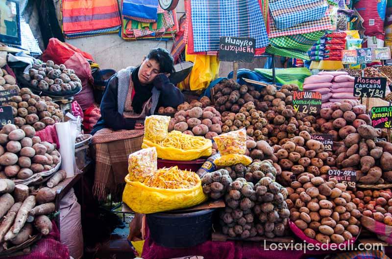 mujer dormida apoyada en su brazo en el puesto de patatas donde trabaja